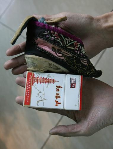 Una scarpina appartenuta ad una donna con i piedi fasciati in confronto ad un pacchetto di sigarette